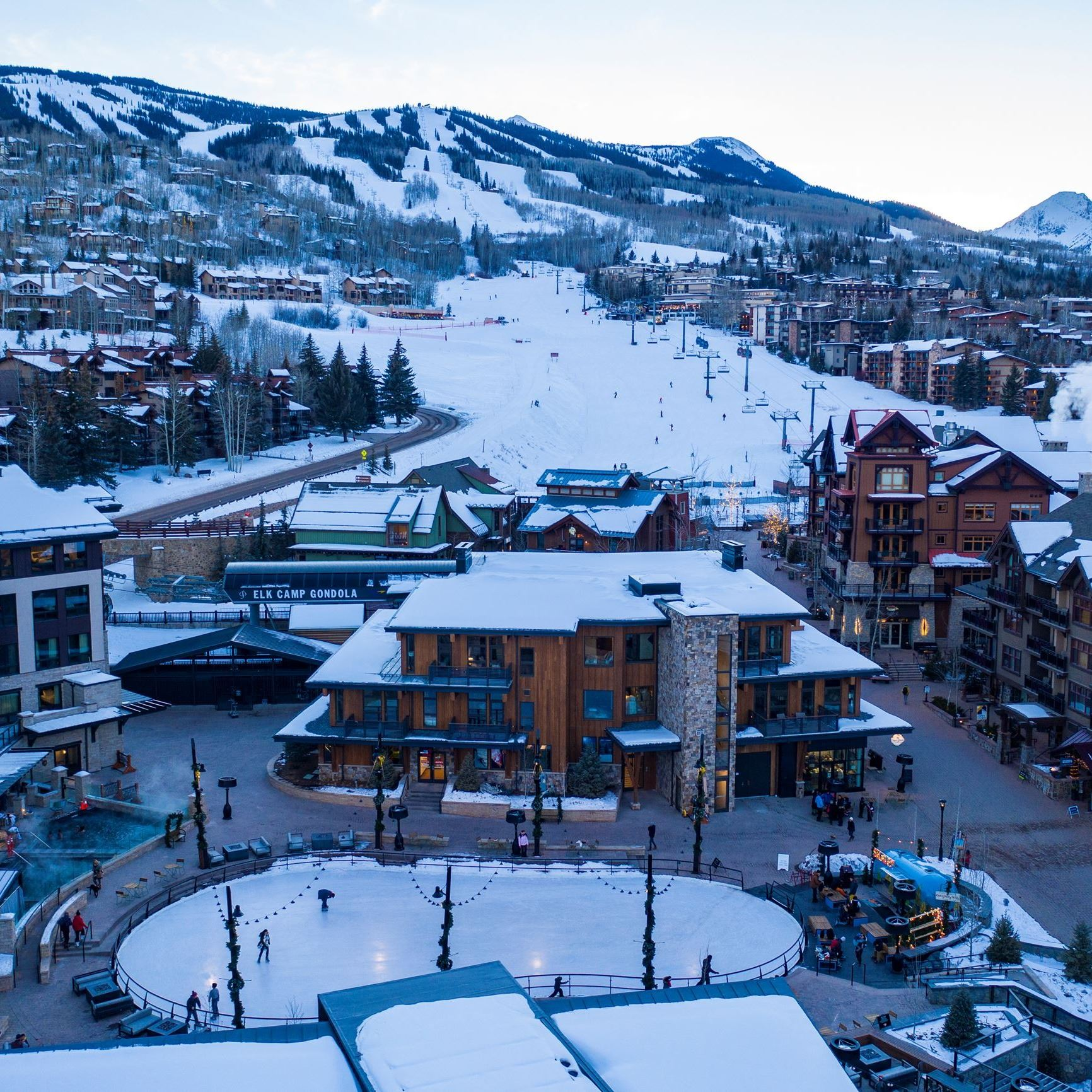 Drone photo looking at snowmass mountain from base village, overlooking ice rink in the winter time