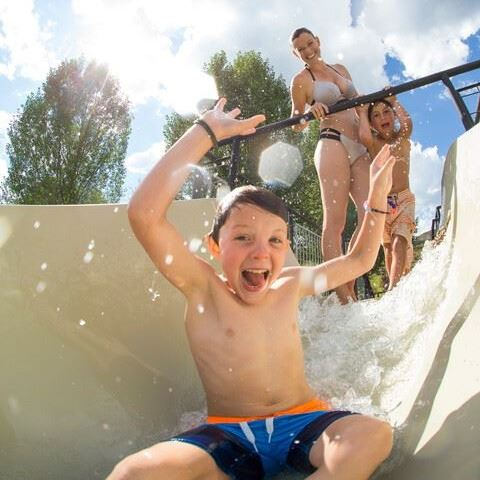 Kid riding down water slide, smiling